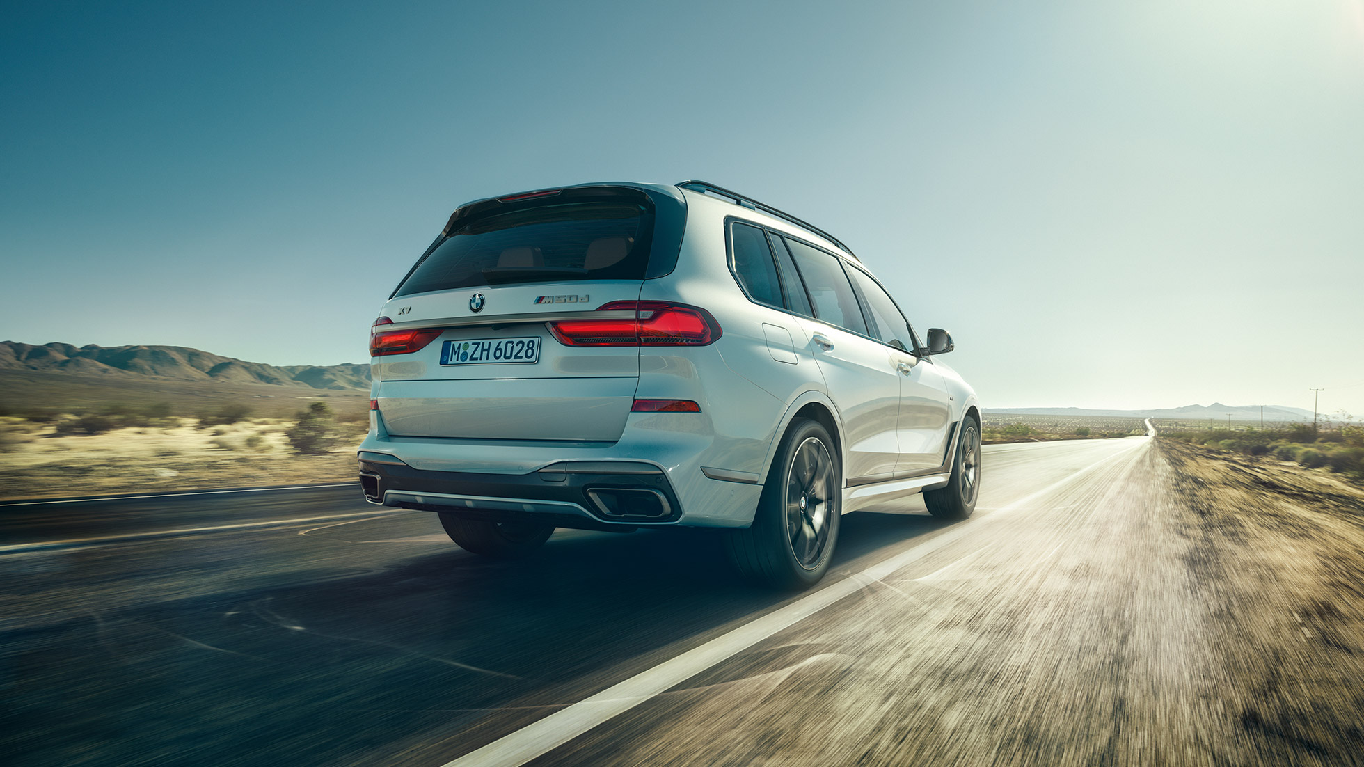 BMW X7 M50d: rear shot of the driving, white BMW X7