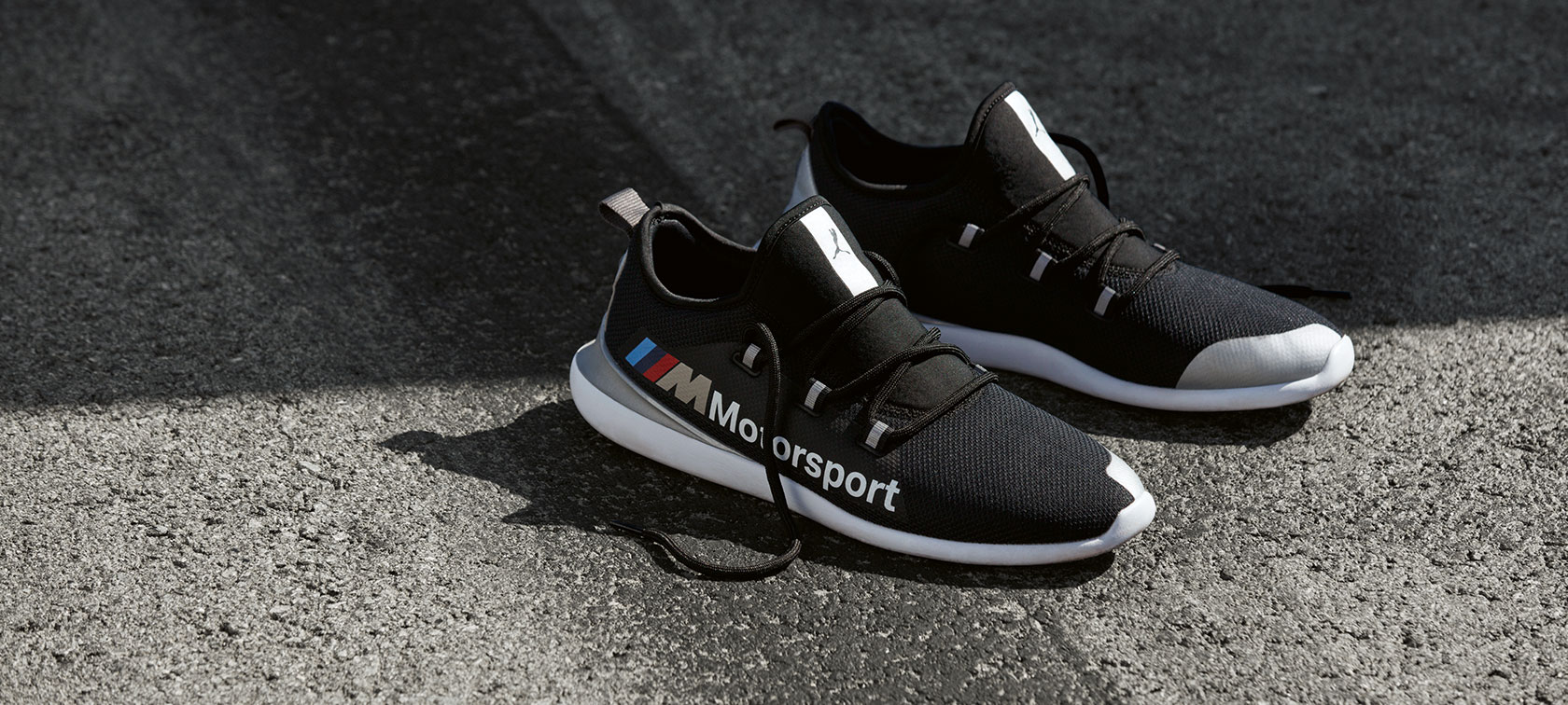 A pair of BMW M Motorsport PUMA EVO CAT Shoes from the BMW M Motorsport Collection is shown standing on a tarmac surface.